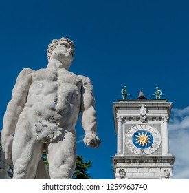 The statue of Hercules with the clock tower of the San Giovanni colonnade, Piazza della Libertà, Udine, Friuli, Italy