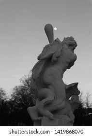 Statue of Hercules fighting the hydra in the gardens of the castle in Karlsruhe in black and white. The club of Hercules is directed in a way that it will seemingly hit the moon.