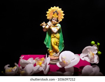 Statue of hindu god Krishna on black background with orchid flowers. Copy space.