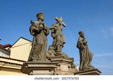 Statue of the Holy Savior with Cosmas and Damian in winter sunlight on Charles Bridge in Prague, Czech Republic.