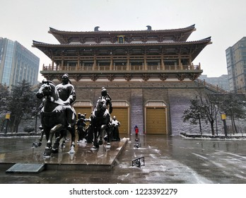 Statue of horsemen in front of chinese building in Qujiang district, Xian city, Shaanxi province, China. Snow in winter season. Chinese architecture.