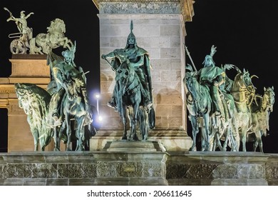 Statue of Hungarian tribal chieftains. Millennium Monument at night - major attraction of city, with 36 m high Corinthian column in center. Heroes' Square, Budapest, Hungary.