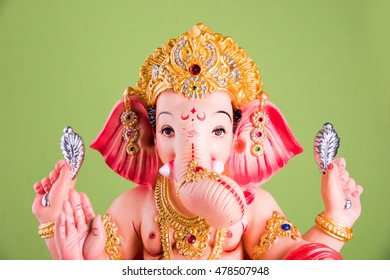 A statue of an Indian god, Lord Ganesha on colourful background.
