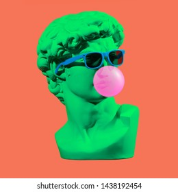 Statue. Isolated. Gypsum statue of David's head. Man. Creative. Plaster statue of David's head in blue sunglasses. Minimal concept art.