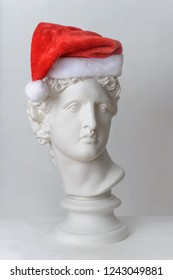 Statue. Isolated. Head. Gypsum statue of Apollo's head.  Statue Apollo's head in Santa Claus hat isolated on white background. Christmas and New Year celebration. Christmas hats.