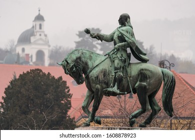 statue of Janos Hunyadi on Szechenyi Square in Pecs, Hungary with chapel at background