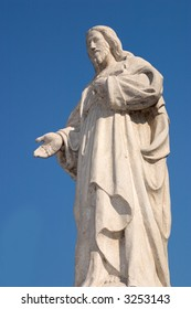 Statue of Jesus against a clear blue sky, taken from the side