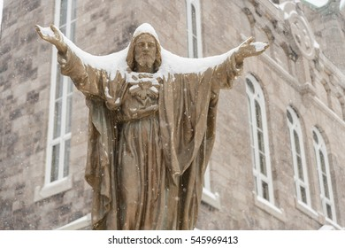 A statue of Jesus Christ covered in snow  in Montreal's Plateau neighborhood, Quebec, Canada