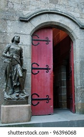 A statue of Joan of Arc stands outside a red door at the Church of St. Pierre, Mont St. Michel, France