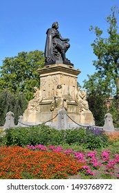 The statue of Joost van den Vondel (unveiled in 1867), designed by sculptor Louis Royer and located inside Vondelpark, Amsterdam, Netherlands. The monument is surrounded by colorful flowers