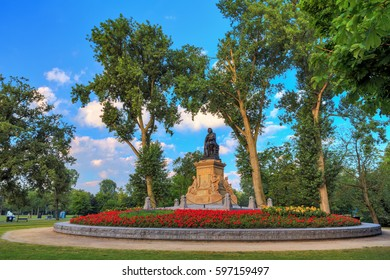 Statue of Joost van den Vondel (1867) with tulips in the Vondelpark in Amsterdam, the Netherlands, on a beautiful spring morning
