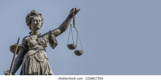 Statue a judge woman with scales and sword at smooth blue background in Frankfurt, Germany