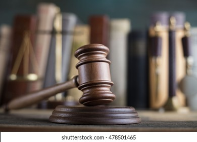Statue of justice, golden scales of justice, gavel and books on brown background. Law code