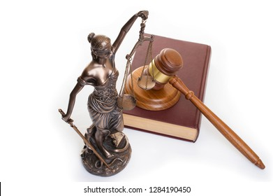 statue of justice, judge's hammer behind books on a white background. Top