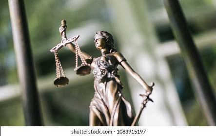The Statue of Justice - lady justice or Iustitia / Justitia the Roman goddess of Justice against a prison grid, legal law concept image