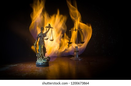 The Statue of Justice - lady justice or Iustitia / Justitia the Roman goddess of Justice on a dark fire background. Selective focus