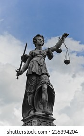Statue of Justice with sword and scales in front of a blue cloudy sky