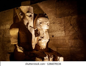Statue of King Tutankhamen and his Queen at Temple of Luxor in Luxor city (Thebes) in Egypt, illuminated at night