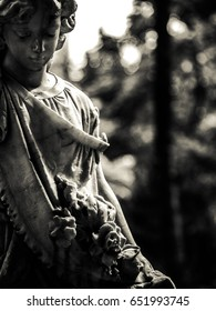 A statue of a lady with roses at an old cemetery. Photo was taken in black and white with blurry background.