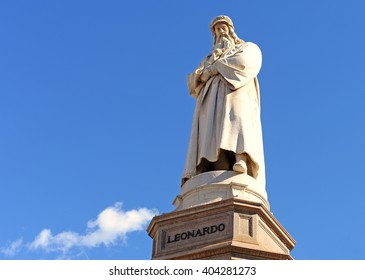 statue of leonardo da vinci against blue sky with a fluffly white cloud on e bright spring day in milan, italy