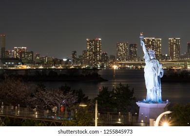 Statue of Liberty in the bay of odaiba, with beautiful buildings with night lights. Night in Odaiba, Tokyo.