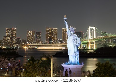 Statue of Liberty in the bay of Odaiba. Behind the beautiful rainbow bridge with night lights. Night in Odaiba, Tokyo.