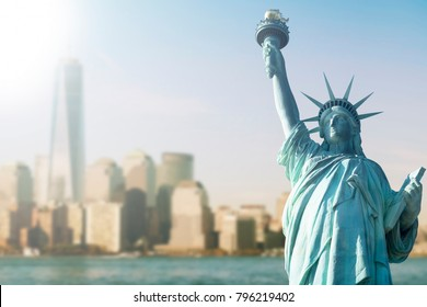 STATUE OF LIBERTY WITH BLUR BACKGROUND OF ONE WORLD TRADE CENTER AND SKYSCRAPERS IN MANHATTAN, NEW YORK, USA