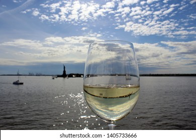 Statue of Liberty in distance with glass goblet of white wine in foreground in early evening. Setting sunlight sparkles on water. Mirror image of skyline in wineglass.