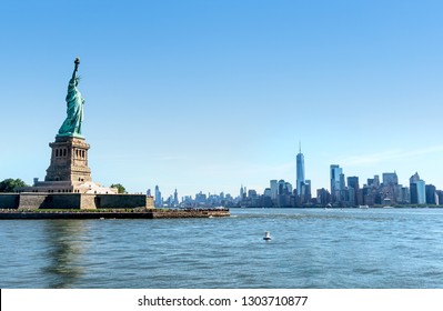 Statue of Liberty with Manhattan skyline in New York. Panorama view to the downtown of NYC. Tourists sightseeing in Liberty Island. NY building and skyscrapers in the background.