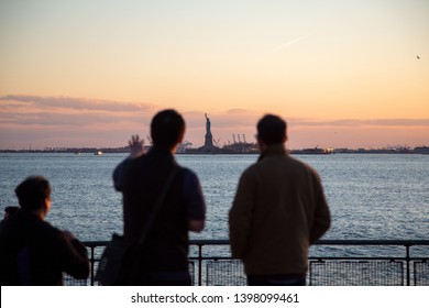 Statue of Liberty New York. People looking at famous Statue of Liberty monument. Beautiful sunset skyline view from Battery Park, FiDi, Lower Manhattan Downtown.