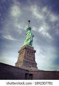 The Statue of Liberty pointing toward blue sky as seen from below