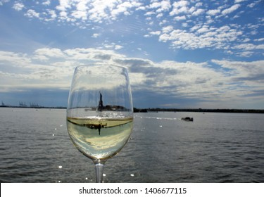 Statue of Liberty reflected in glass goblet of white wine as seen from Hudson River in early evening. Setting sunlight sparkles on water. Mirror image of Statue in wineglass.
