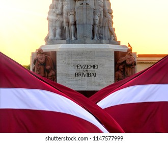 Statue of Liberty in Riga, background filled with the state Latvia flag , sunrise behind of monument