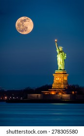 Statue of Liberty and a rising supermoon in New York City