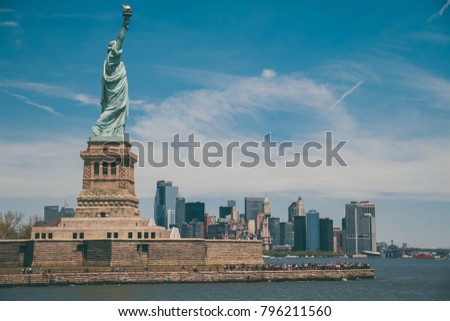 Statue of Liberty in side view and Manhattan with water in vintage style New York