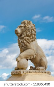 Statue of a lion with ball against a blue sky