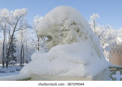 Statue of the lion under snow in Alexander park of Pushkin