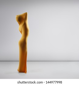 statue made of perfect sexy female body in yellow fabric posing at studio