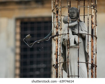 Statue of the Madonna and baby Jesus in a cage in a prison recreation area (Italy)