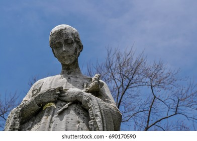 Statue of a man in a cemetery above a grave