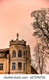 Statue of a man on top of the old building in Kuldiga, Latvia at dusk. One window is missing. Artistic altered vanilla skies.