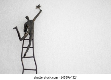 Statue of a man reaching for a star