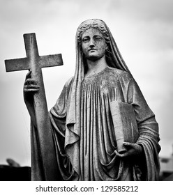 Statue of Mary with a bible and a cross on the cemetery, with creepy look.