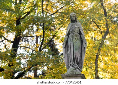 Statue of Mary Mother of God, at autumn tree backgroung, copy space. Religious symbol.