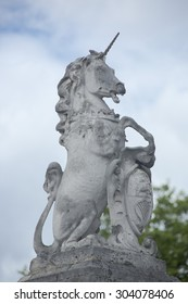 Statue of the mythical creature the Scottish Unicorn with shield and Scottish coat of arms sitting on gatepost outside Buckingham Palace London UK symbolising the free union of Scotland and England.