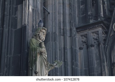 Statue on the front of the Cathedral in Cologne, with a pigeon on the head.