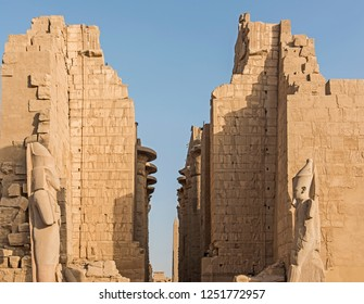Statue of pharaoh and large stone wall at temple of Karnak courtyard in Luxor Egypt