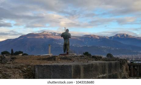 Statue in Pompeii ruins with volcano Vesuvius