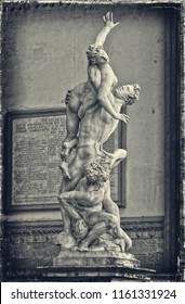 Statue The Rape of the Sabine Women shows the moment one of the women was stolen from her husband, with the captor crushing him against a rocks. Black White Photography. Sculptures in Florence, Italy