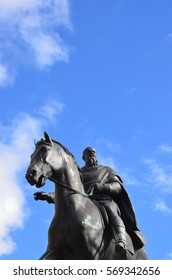 Statue of a rider on a horse at lightly cloudy sky and sunshine